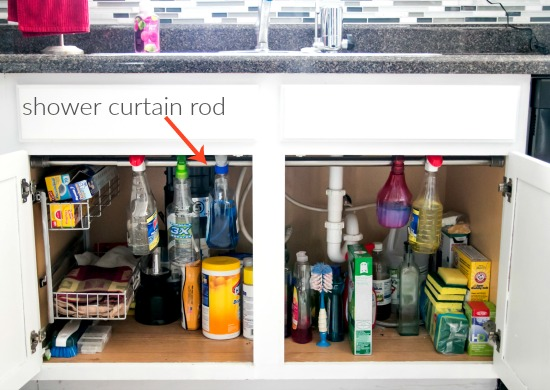 kitchen organizing use shower curtain rod to hang cleaning bottles and give more storage space under the sink